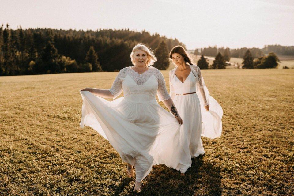 kurvige Braut auf der Wiese vor schlanker Braut