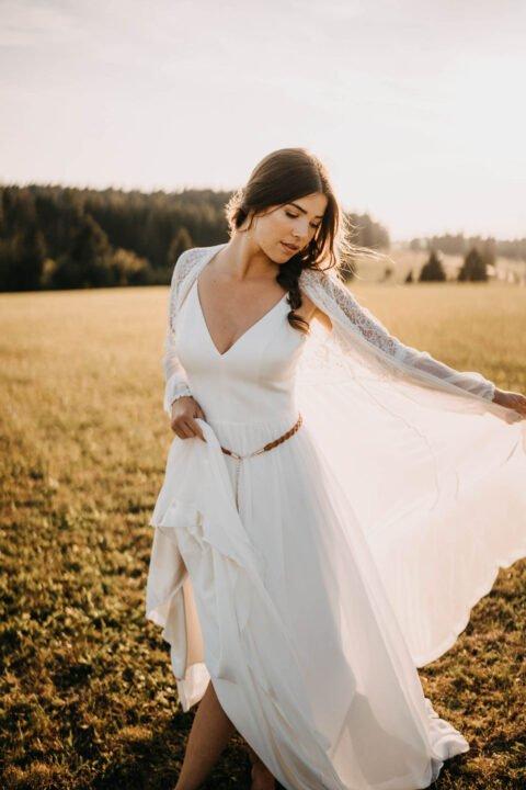 schöne Braut im schlichten Brautkleid mit Seidenmantel auf der Wiese