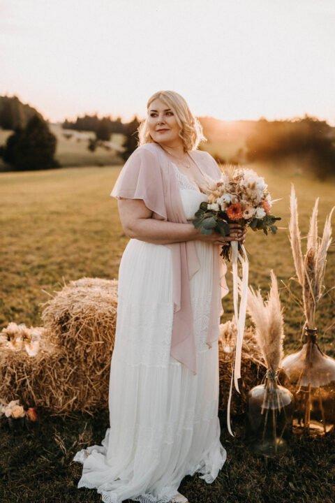 kurvige Braut mit Brautstrauß vor Heuballen auf der Wiese