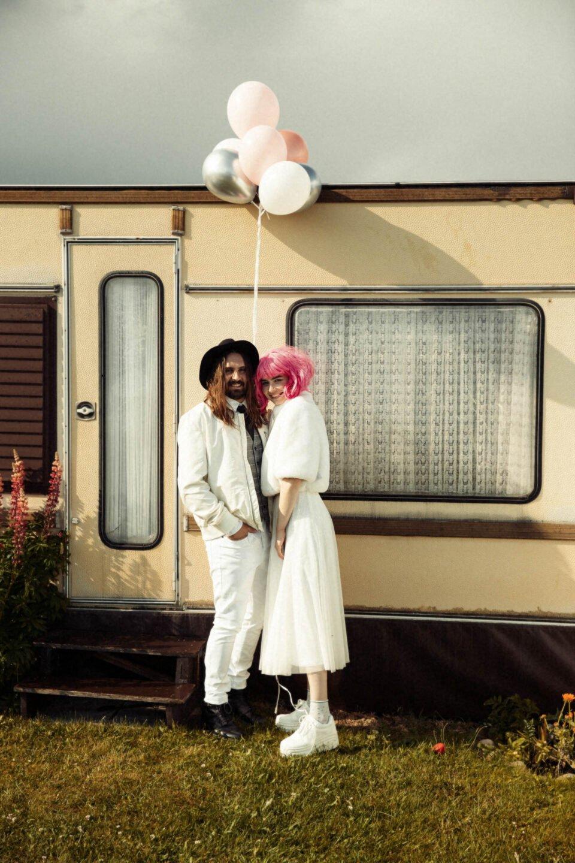 Brautpaar mit Luftballons vorm Wohnwagen