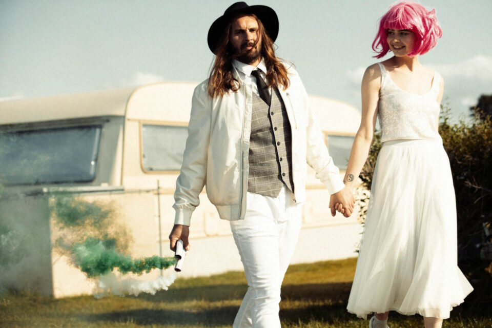 Brautpaar Hand in Hand auf dem Campingplatz, der Bräutigam hält Farbfackeln in der Hand