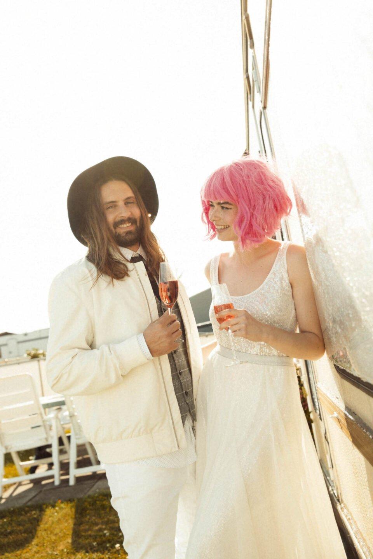 White Glamping, Brautpaar stößt auf dem Campingplatz mit Sekt an
