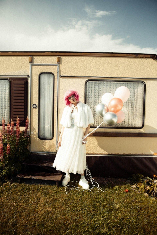Sytlische Braut mit Luftballons vorm Waohnwagen
