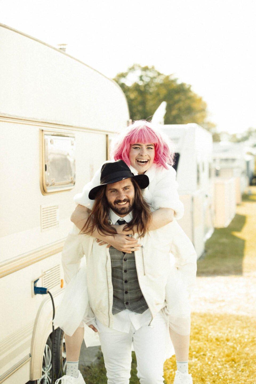 White Glamping, Bräutigam trägt Braut vor Wohnwagen Huckepack