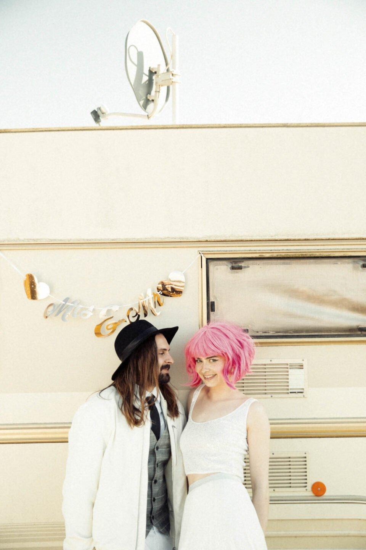 White Glamping, cooles Brautpaar mit Mr and Mrs Girlande vorm Wohnwagen