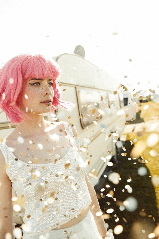 Braut mit pinker Perücke im Konfettiregen