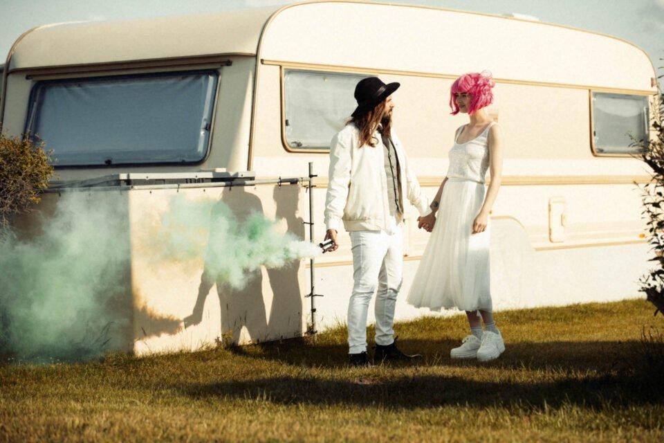 White Glamping mit coolem Brautpaar, der Bräutigam hält Farbfackeln in der Hand