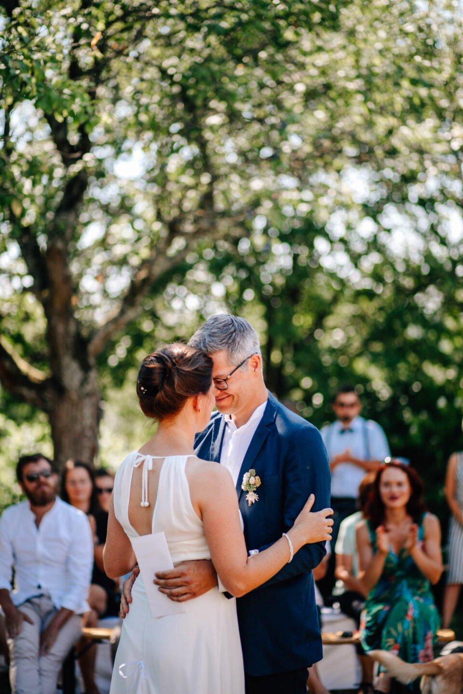 Brautpaar umarmt sich nach Trauversprechen auf der Wiese