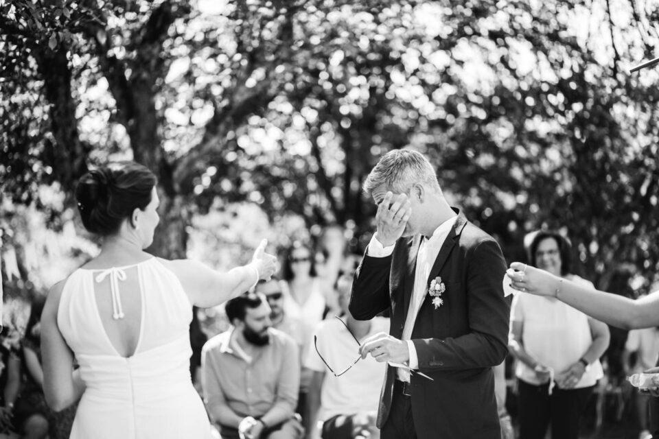 gebrühter Bräutigam wischt sich Träne aus den Augen bei Trauversprechen an der Gartenhochzeit