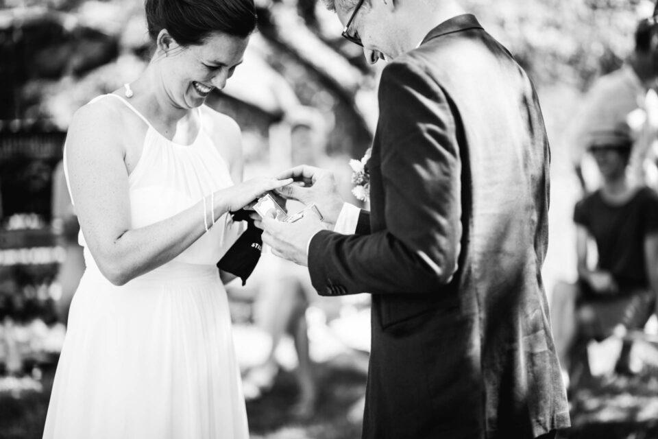Bräutigam steckt der Braut den Ehering bei Hochzeit im Garten an