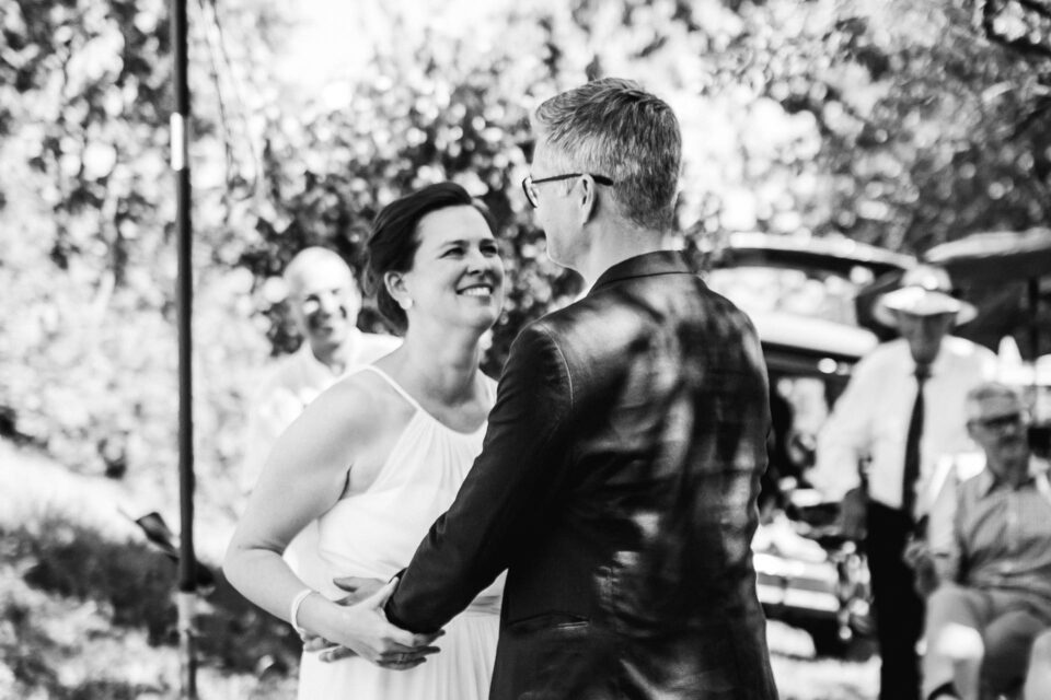 Braut himmelt Bräutigam bei Gartenhochzeit nach Eheversprechen an
