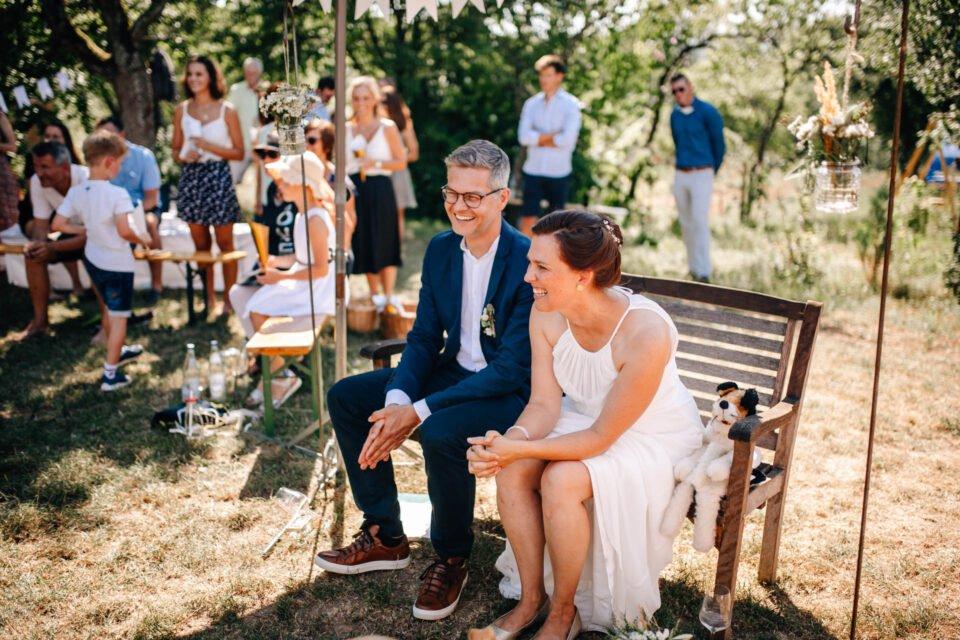lachendes Brautpaar bei Gartenhochzeit auf einer Bank