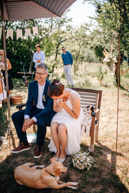 Glückliches Brautpaar mit Hund bei Gartenhochzeit