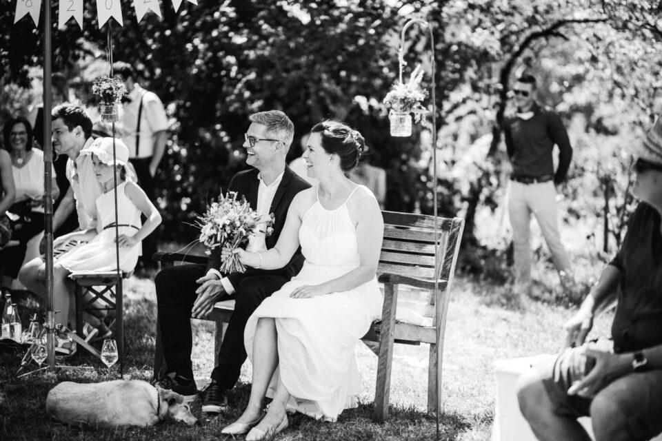 Brautpaar auf einer Bank auf der Wiese vorm Trauversprechen bei ihrer Gartenhochzeit