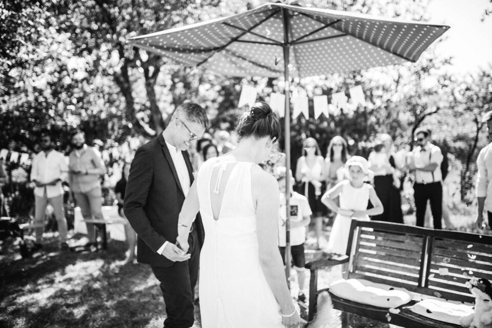 Braut und Bräutigam Hand in Hand nach Eheversprechen bei Gartenhochzeit