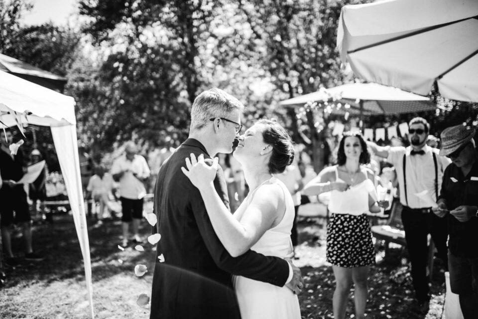 Brautpaar küsst sich bei Gartenhochzeit