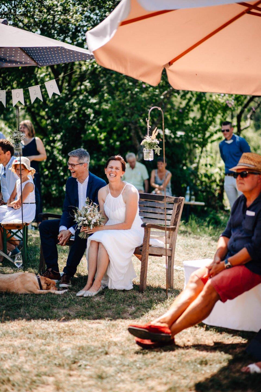lachendes Brautpaar unter freiem Himmel auf einer Bank bei Gartenhochzeit