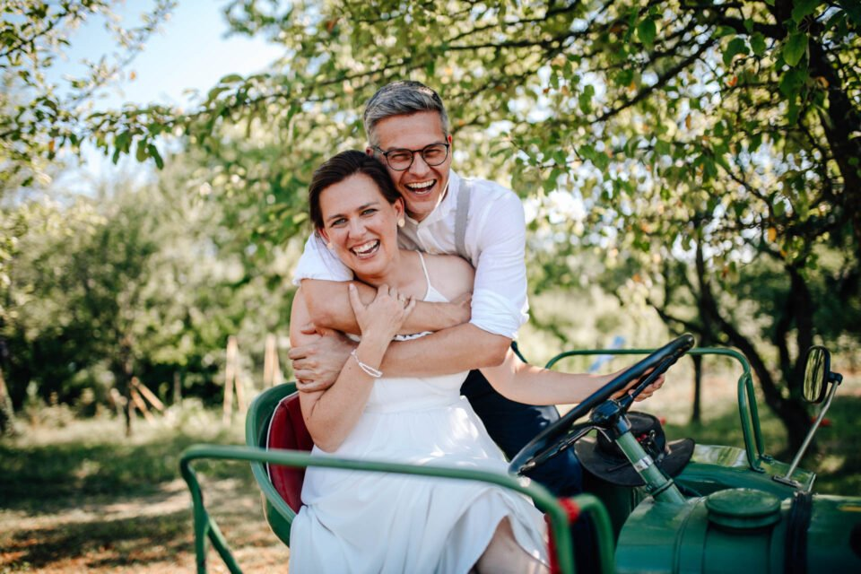 lachendes Brautpaar auf Traktor bei Gartenhochzeit