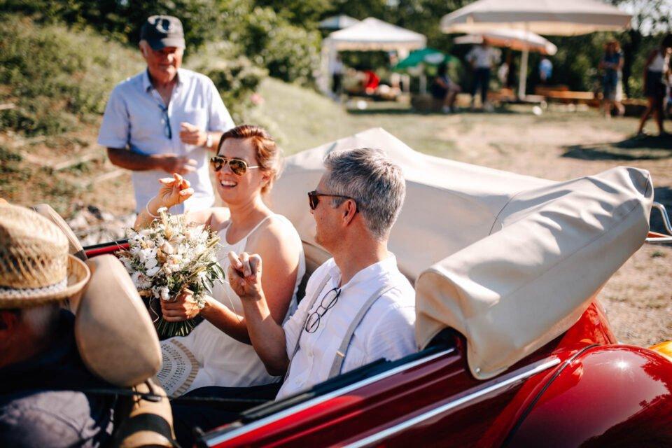 Brautpaar nach Gartenhochzeit im Cabrio