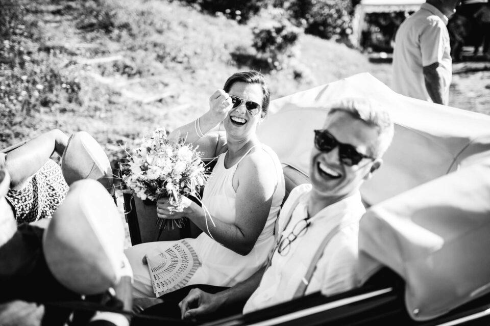 Lachendes Brautpaar im Auto, Braut zeigt ihren Ehering an der Hand