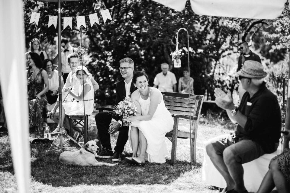 lachendes Brautpaar vor dem Trauversprechen auf einer Bank bei Gartenhochzeit