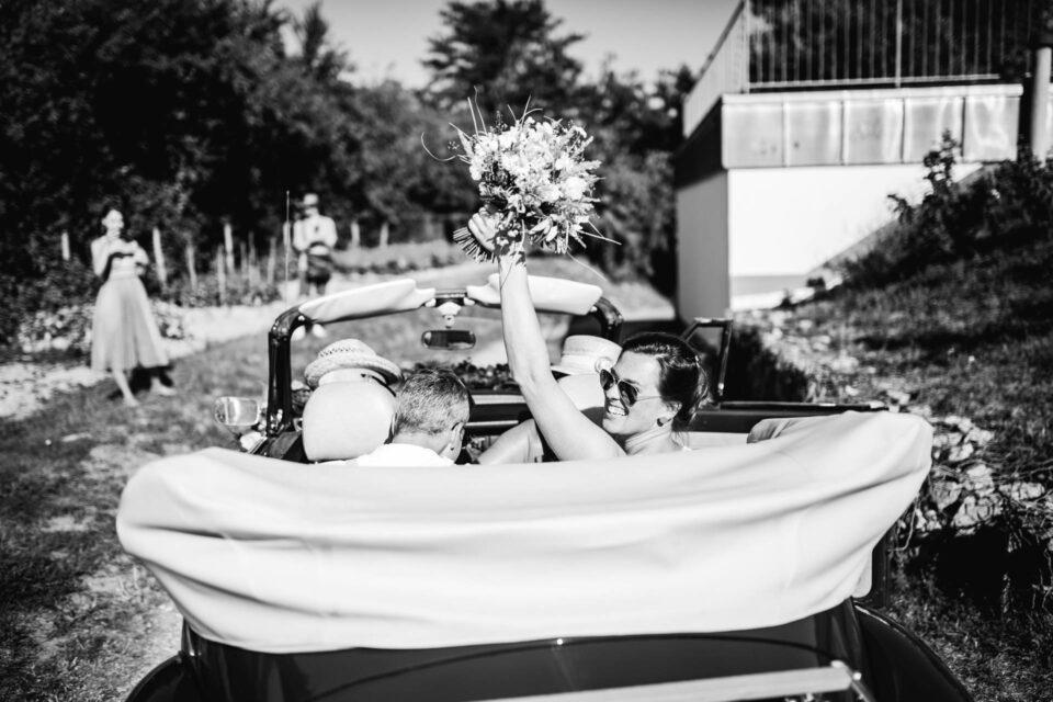 Brautpaar lässt sich im Cabrio nach Gartenhochzeit zur Hochzeitslocation fahren