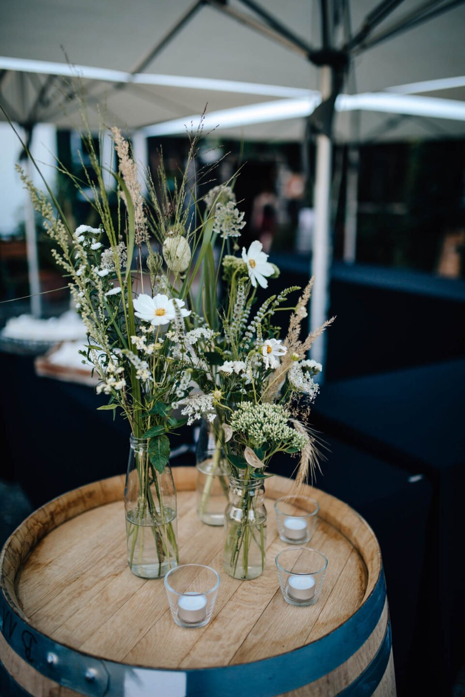 Blumen in Vase auf Weinfaß in der Hochzeitslocation