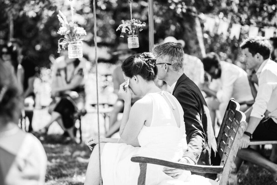 Braut tupft sich Tränen ab bei Hochzeit auf der Wiese