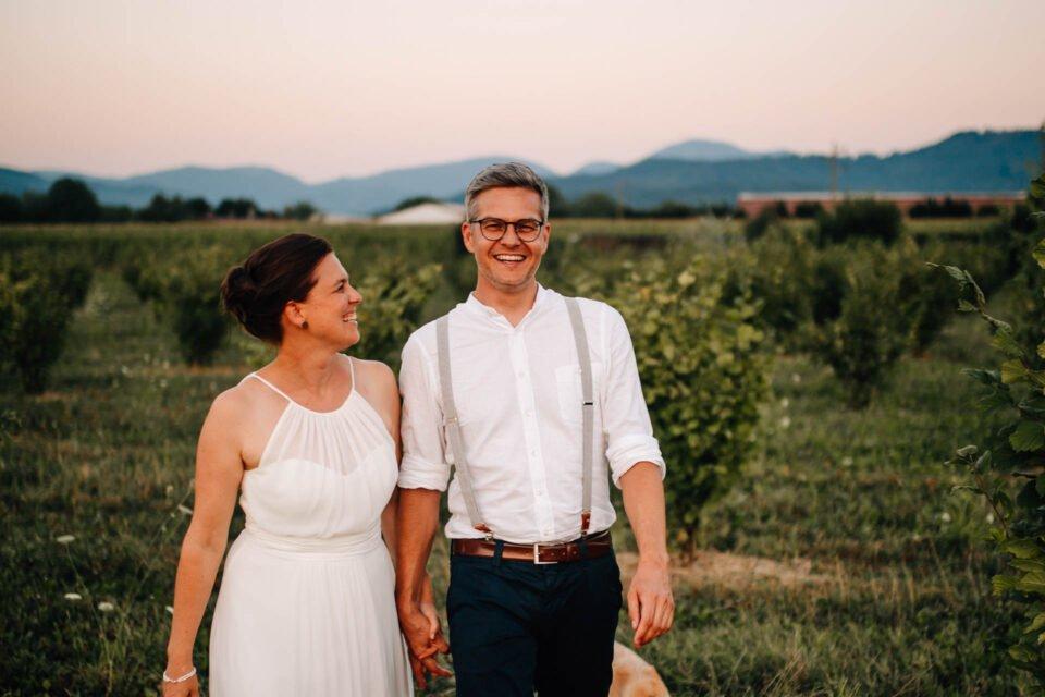lachendes Brautpaar Hand in Hand auf Wiese