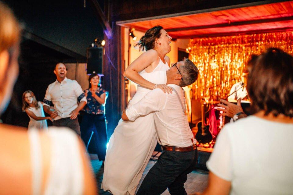 Bräutigam versucht Hebefigur mit Braut auf der Tanzfläche