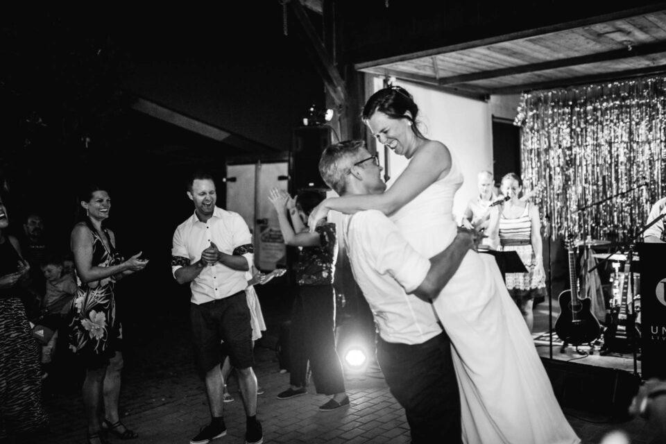 Bräutigam hält Braut auf der Tanzfläche hoch