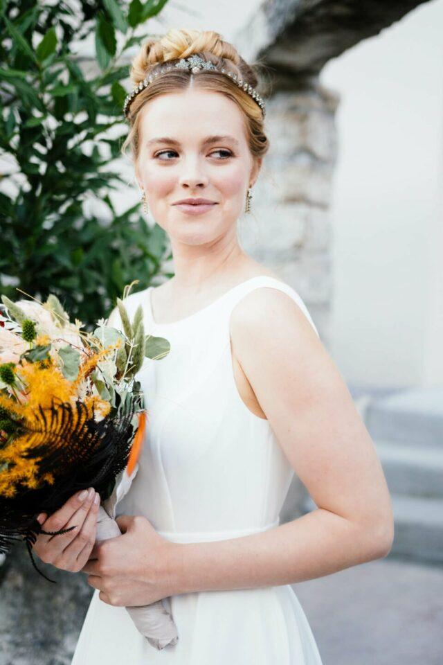 Hochzeitskleid mit Trägern, Braut strahlt mit buntem Brautstrauß in der Hand