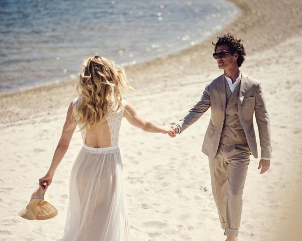 Boho Brautkleid rückenfrei am Strand, Braut und Bräutigam Hand in Hand