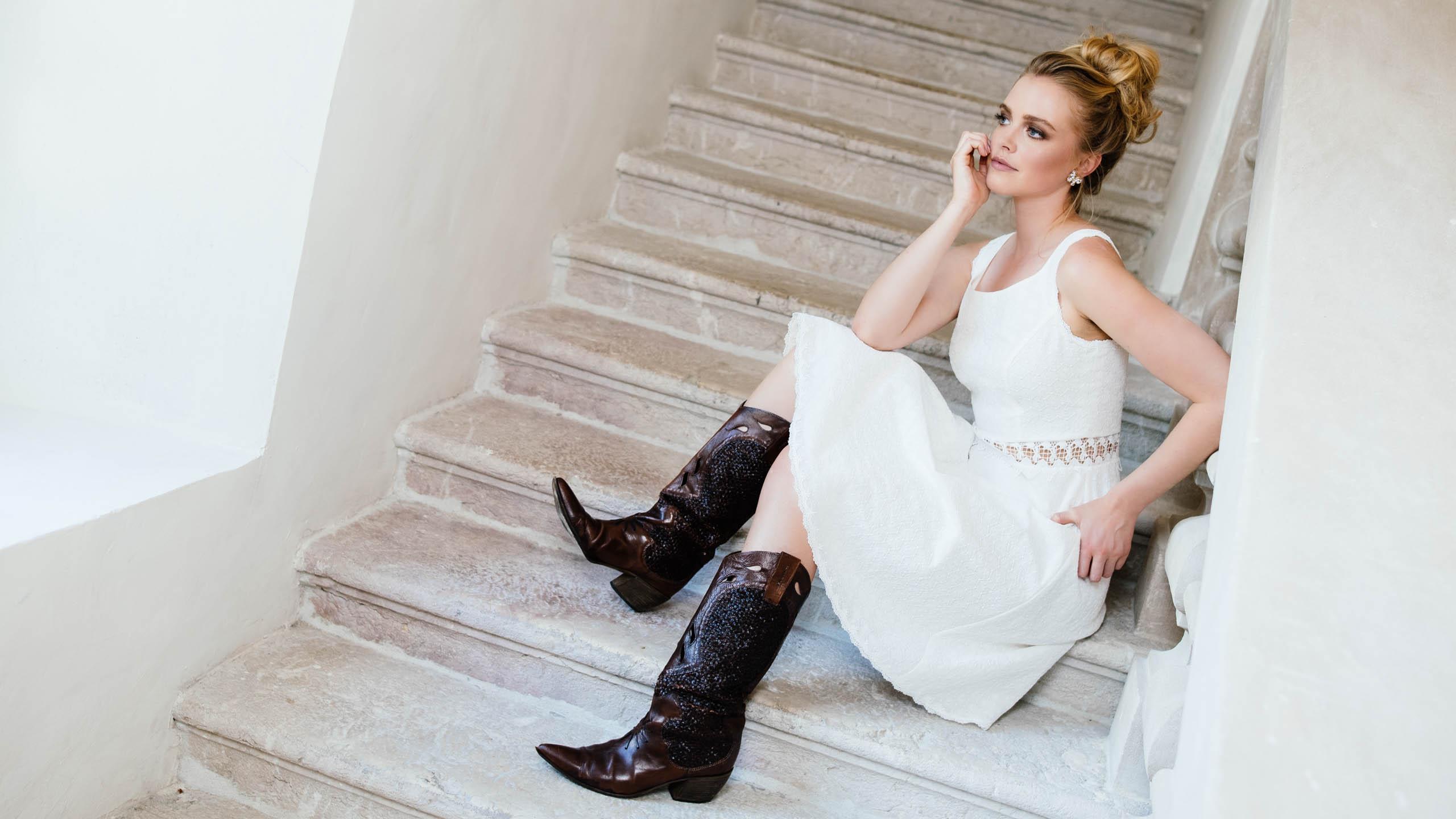 Kurzes Brautkleid mit Cowboystiefeln kombiniert, Braut sitzt auf der Treppe