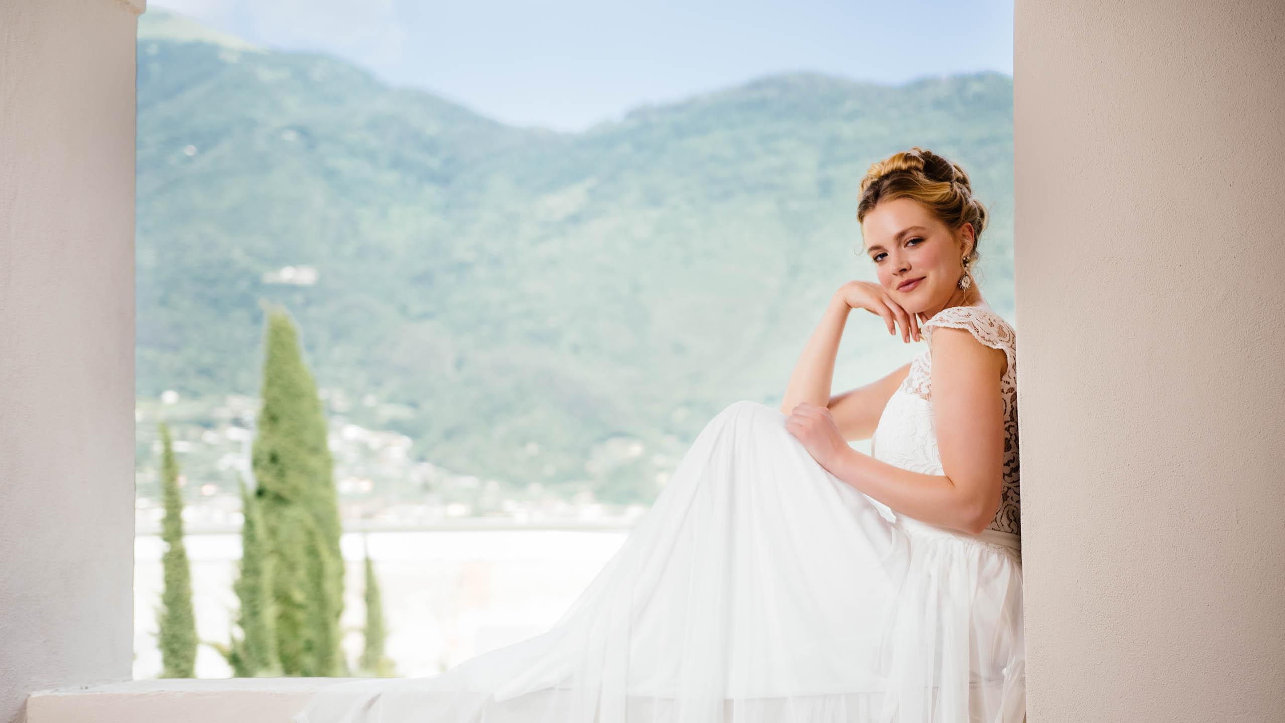 Braut sitzt mit Bohemian Hochzeitskleid auf dem Balkon