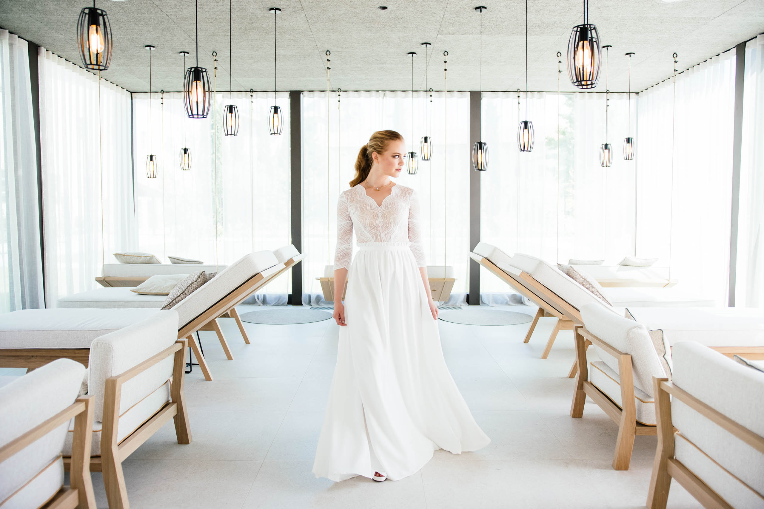 Braut läuft im langen Brautrock mit Spitzenbody