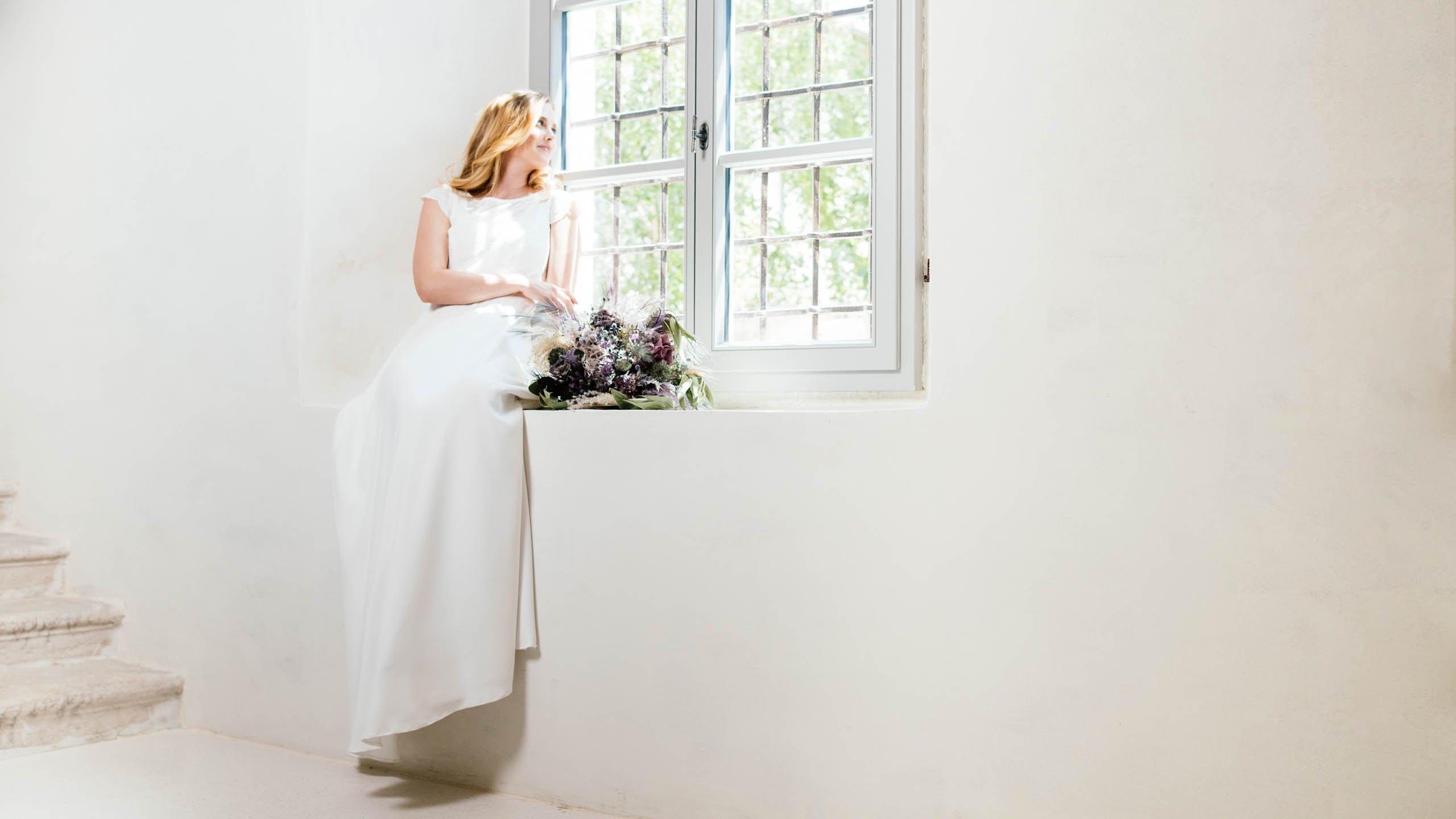 Braut im Eco Brautkleid schaut aus dem Fenster, neben ihr liegt ein Trockenblumen-Brautstrauß der Fensterbank