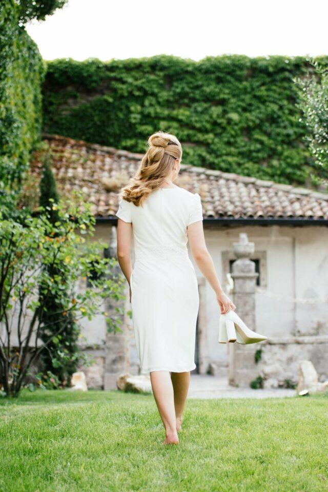 Braut barfuß mit Pumps in der Hand von hinten im schmalen Etui Hochzeitskleid