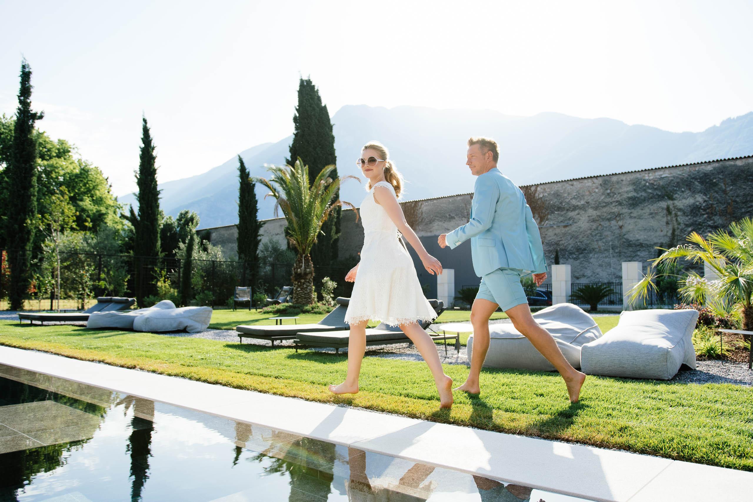 Brautpaar barfuß am Pool, Braut mit Sonnenbrille im kurzen Brautkleid, Bräutigam im kurzen Anzug