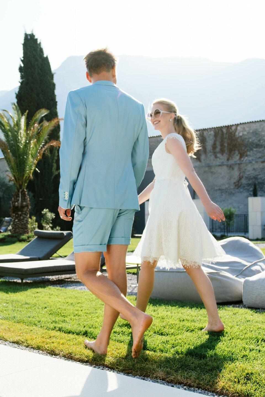 Bräutigam im kurzen Hochzeitsanzug, Braut im kurzen Brautkleid aus recycelter Spitze