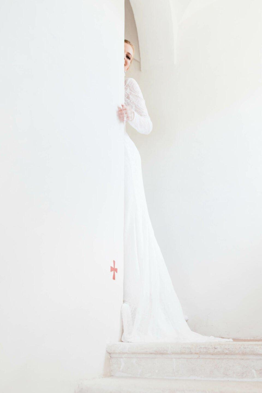 Braut mit Langarm Brautkleid verschwindet hinter der Mauer