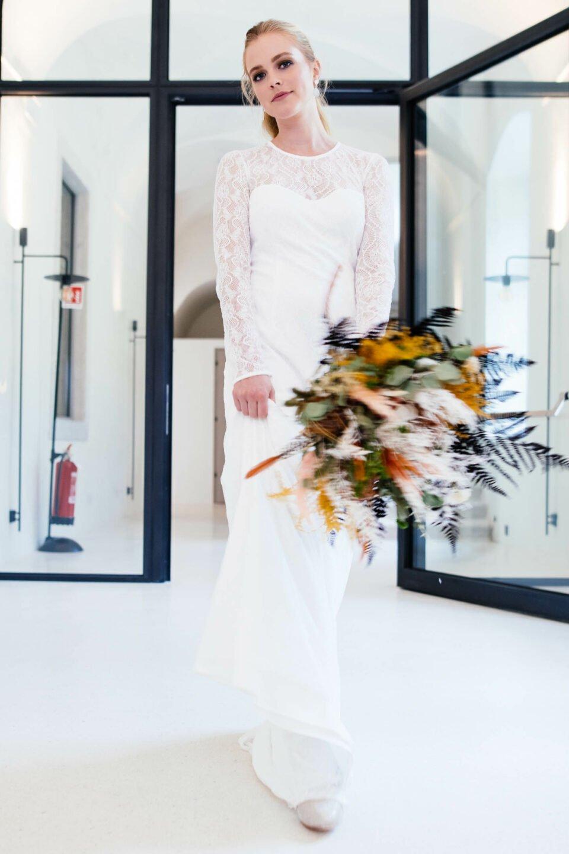 Braut mit Brautstrauß in edlem Hochzeitskleid Allover aus nachhaltiger Spitze