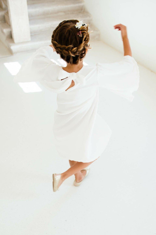 Blumenkind dreht sich im Kleid und hat Spaß an der Hochzeit